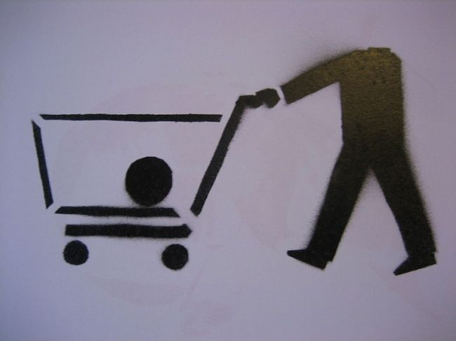 Stencil of a shopping cart with the head of the consumer in the cart. An image from the spanish subvertising group ConsumeHastaMorir, www.consumehastamorir.org